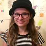 A picture of Z, an agender teenager wearing a bowler hat and black-frame glasses, standing in front of a collage.