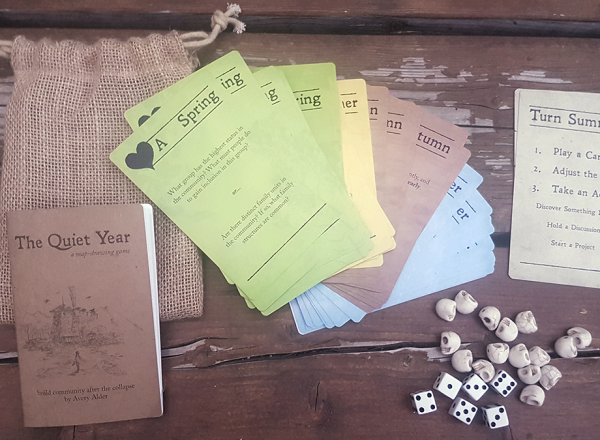 A small burlap bag, next to its unpacked contents: a booklet, cards, dice, and tokens.